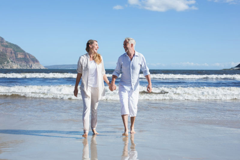 elderly couple walking along the beach